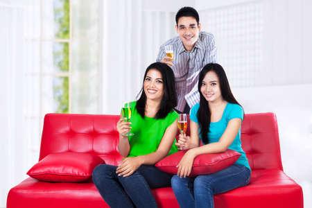 tomando vino: Felices tres amigos jóvenes con el vino que se sientan en el sofá rojo Foto de archivo