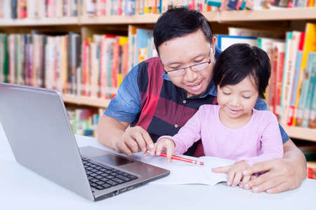 chinese adult: Image of lovely little girl studying in the library and learn to write on the book with a male teacher Stock Photo
