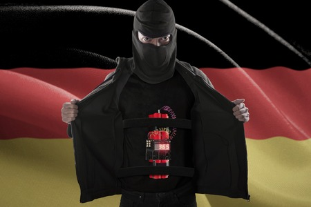 detonating: Terrorism concept: Terrorist sticking a time bomb on his body for suicide attack in front of German flag Stock Photo