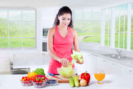 super woman: Beautiful indian woman with sportswear preparing healthy superfood in the kitchen