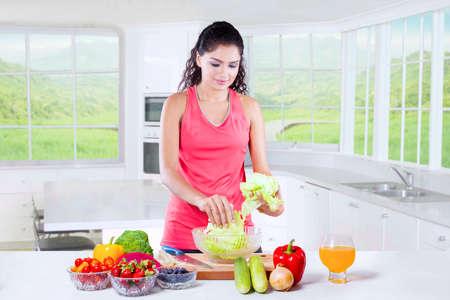 ropa deportiva: Mujer india hermosa con ropa deportiva preparar súper alimento saludable en la cocina