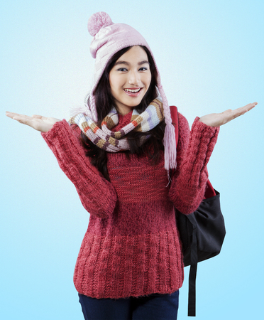 school teens: Portrait of pretty student carrying backpack and wearing a knitted winter clothes