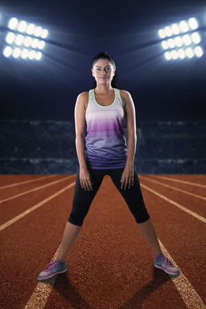 woman standing: Portrait of indian woman wearing sportswear standing on the track and ready to workout