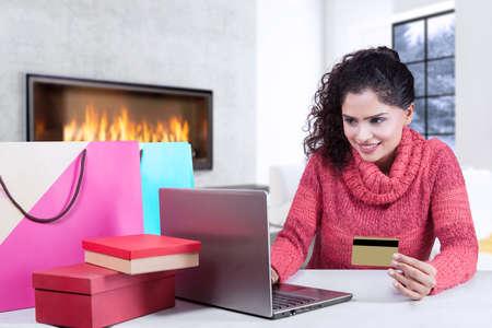 Jeune femme indienne sourire heureux tout en utilisant la carte de crédit et un ordinateur portable pour faire des achats en ligne avec des sacs sur le bureau Banque d'images - 48741273