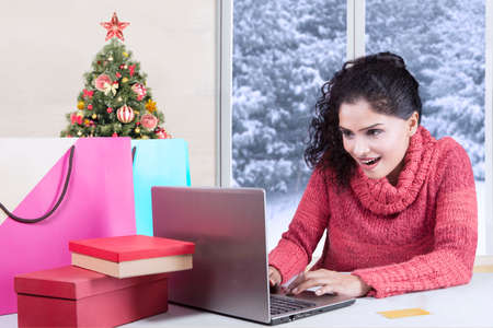 asian shopper: Photo of suprised pretty indian woman with winter clothes, shopping online at home with laptop and shopping bags on desk