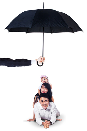 umbrella: Image of two cheerful parents and their daughter lying in the studio under umbrella. Life and family insurance concept
