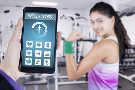 muscle training: Bild von Hand hält Smartphone mit Gewichtsverlust Anwendung und Hintergrund der gesunden Frau, die ihre Bizeps im Fitnessstudio zeigt