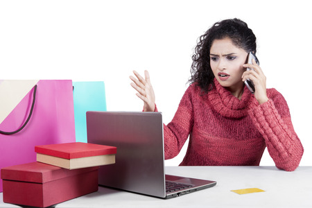 complaining: Young indian woman looks disappointed after shopping online and complaining by phone with laptop and shopping bags on the table Stock Photo