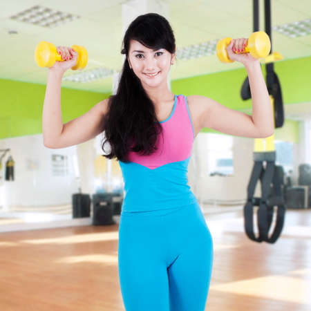 asian bodybuilder: Portrait of beautiful healthy woman uses two dumbbells to train her biceps at fitness center