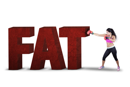 gordos: mujer sana que lleva dos guantes de boxeo para perforar un texto de grasa en el estudio, aislado en blanco Foto de archivo