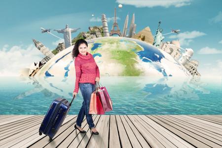 alrededor del mundo: Mujer india bonita con ropa de invierno y vacaciones de todo el mundo en el ejercicio de la maleta y bolsas de compras