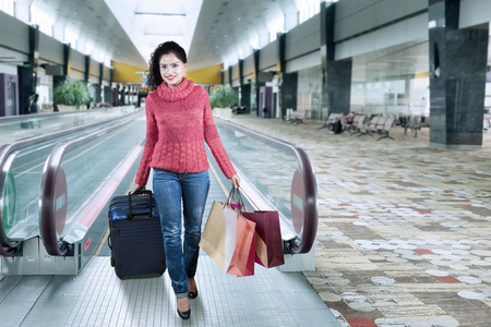 Happy indian woman wearing winter clothes and walking in the airport hall while carrying suitcase and shopping bags Stock Photo