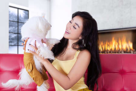 dogie: Pretty young woman sitting on the sofa while holding her dog, shot at home