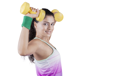 asian bodybuilder: Portrait of young indian woman smiling at the camera while doing exercise with two dumbbells in studio