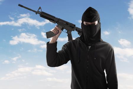 gaze: Scary terrorist with cold gaze, wearing mask and holding machine gun, shot outdoors