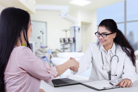 Portret van vriendelijke Indiase arts handshaking met haar patiënt in het ziekenhuis