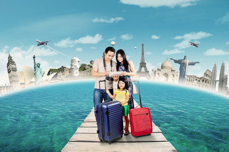 reisen: Schöne Familie Tragetaschen und Verwendung Tablette, um zu sehen und wählen Sie der Welt Denkmal