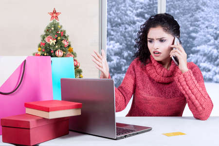 angry person: Portrait of angry indian woman talking on the phone while complaining after shopping online with laptop and shopping bags on desk