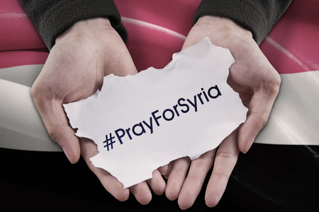 pray: Image of two hands holding a paper with text of Pray for Syria with Syrian flag background