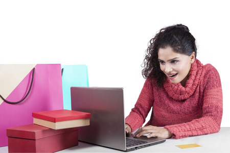 happy shopper: Image of happy indian woman wearing winter clothes and using laptop computer for shopping online with shopping bag on desk Stock Photo