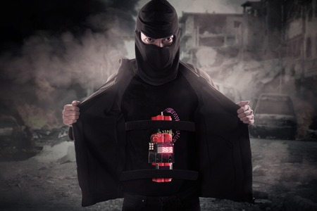 detonating: Image of male terrorist wearing mask and showing time bomb on his body at damaged city