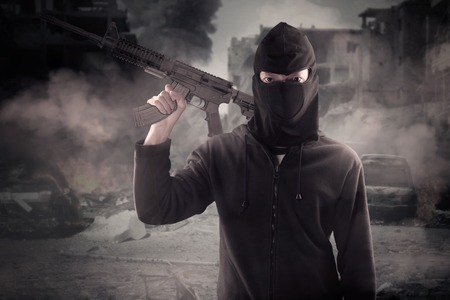 aggression: Image of male terrorist wearing mask and carrying machine gun at the broken city