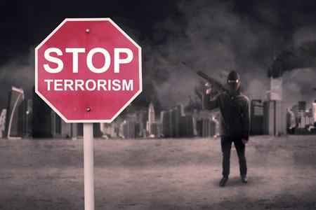 conflicto: La señal de tráfico con el texto de detener el terrorismo y terrorista varón llevaba una ametralladora cerca de la ciudad dañada