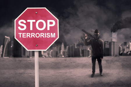 stop: Road sign with text of Stop Terrorism and male terrorist carrying a machine gun near the damaged city