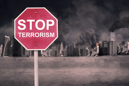 terrorism: Stop Terrorism concept: Road sign with text of Stop Terrorism near the damaged city