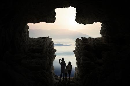 sacra famiglia: Silhouette di due genitori ei loro bambini in piedi all'interno di grotta a forma di un simbolo della croce