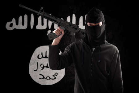 radical: Male terrorist wearing mask and carrying machine gun with flag of ISIS