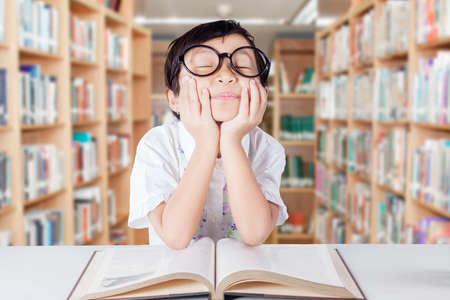 kid book: Image of a little girl daydreaming in the library while studying with a book and wearing glasses