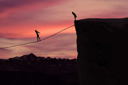hard working woman: Silhouette of young businesswoman called on all her courage to walk on the rope at mountain. Business challenge concept Stock Photo