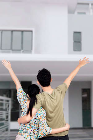 home loan: Young happy family showing their new house