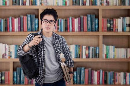 niño con mochila: Estudiante masculino arrogante apuntando a la cámara en la biblioteca
