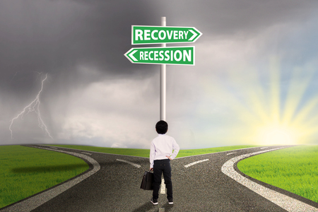 road to recovery: Little businessman standing on the road and looking at a road sign directing to the road of recession and recovery financial Stock Photo