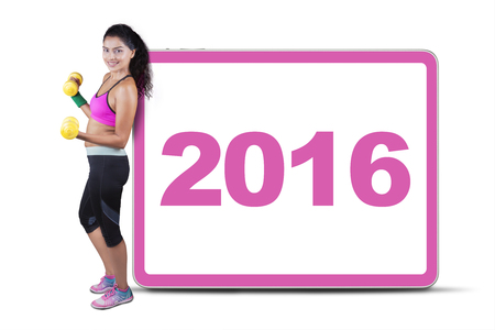 asian bodybuilder: Indian woman holding dumbbells and wearing sportswear, leaning on a billboard with numbers 2016