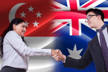 singaporean: Photo of young Singaporean businesswoman shaking hands with Australian businessman in front of Singaporean and Australian flags