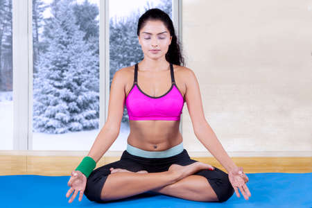 meditating: Image of attractive indian woman wearing sportswear and doing meditation on the mattress at home, shot with winter background on the window Stock Photo