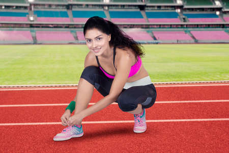 shoes woman: Beautiful indian young woman doing workout at field and tying her shoelaces while smiling at the camera