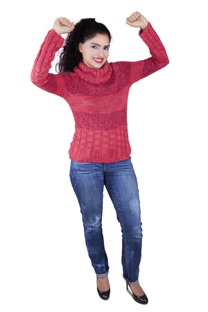 woman standing: Full length of indian young woman standing in the studio while wearing winter clothes, isolated on white background