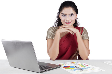 Portrait of indian young businesswoman smiling at the camera while wearing traditional clothes with laptop and financial chart on desk Stock Photo