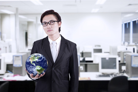asian businessman: Confident asian businessman holding a globe in the office Stock Photo