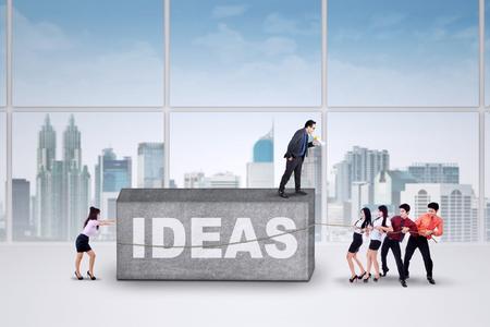 subordinates: Businessman commanding his subordinates to move a business burden with a text of ideas