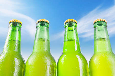 dew cap: Close up of four bottles with dew and fresh beer, shot outdoors under the blue sky