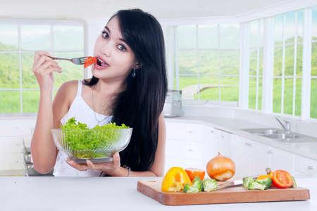 niña comiendo: Imagen de la hermosa mujer joven sosteniendo un plato de ensalada fresca, mientras que comer tomate en la cocina