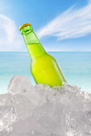 booze: Cold booze in the green bottle with dew and ice cube. Shot at beach under clear sky