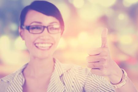 persona feliz: Joven empresaria sonriendo a la cámara mientras muestra el pulgar hacia arriba, disparó contra un fondo del brillo de luz