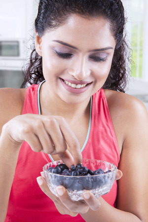 Caucasian woman: Beautiful young woman wearing sportswear and holding a bowl of blueberries at home