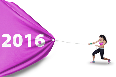 Picture of healthy indian woman wearing sportswear and pulling a big flag with numbers 2016 in studio Banque d'images